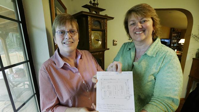 Kim Ridgway, left, and her wife Kimberly Bliss, right, pose for a photo, Wednesday, Feb. 27, 2013 at their home in Lacey, Wash. with a copy of a rough floor plan for the state-licensed marijuana store they hope to open before the end of the year.  The couple got married on Dec. 9, 2012, thanks to the state's new gay marriage law, and now they are trying to take advantage of another measure voters approved in November by planning to open the store. (AP Photo/Ted S. Warren)