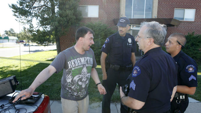 University of Colorado medical school researcher Dimitry Shchekochikhin, left, from Moscow, thanks Aurora police officers after they recovered his computer and some clothes from his apartment at the same apartment house of shooting suspect James Eagen Holmes in Aurora, Colo. on Sunday, July 22, 2012. Shchekochikhin, 27, says he lived in the apartment house since November and had casual contact with Holmes. Holmes has been charged in the shooting at an Aurora theatre early Friday that killed twelve people and injured more than 50. (AP Photo/Ed Andrieski)