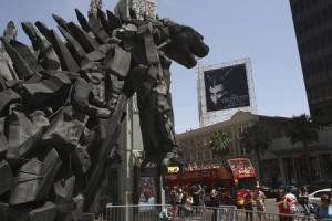 A tourist bus passes a statue of movie monster Godzilla in front of the TCL Chinese Theatre IMAX forecourt on Hollywood Boulevard in Hollywood