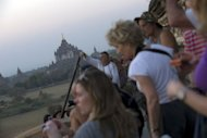 Tourists watch sunset over the pagodas in Myanmar's northern ancient town of Bagan. Myanmar has given approval for the introduction of Visa and other foreign credit cards, whose absence has been a long-standing headache for visitors to the former pariah state