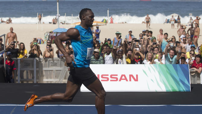 """Jamaican Olympic gold medallist Usain Bolt, front, smiles after crossing the finish line of the """"Mano a Mano"""" men's 100m challenge in Rio de Janeiro, Brazil, Sunday, Aug.17, 2014. (AP Photo/Silvia Izquierdo)"""