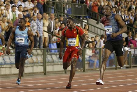 Bolt of Jamaica runs next to Carter of Jamaica and Gatlin of the U.S. on his way to win the men's 100 metres during the IAAF Diamond League athletics meeting in Brussels