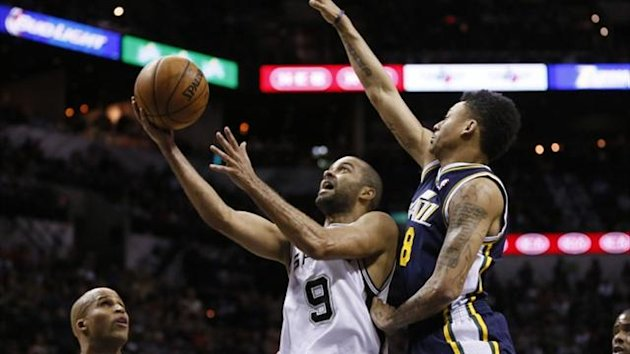 San Antonio Spurs guard Tony Parker (9) drives to the basket under pressure from Utah Jazz guard Diante Garrett (8) during the second half at AT&T Center (Reuters)