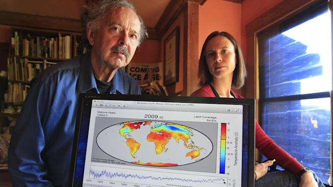 In this Friday, Oct. 28, 2011 photo, Richard Muller, left, and his daughter, Elizabeth Muller, right, pose with a map from their study on climate at their home in Berkeley, Calif. A new study of Earth's temperatures going back more than 200 years finds the same old story: It's gotten hotter in the last 60 years. What's different is the scientist behind the latest study, Richard Muller. The California physicist was doubtful of what climate scientists have been saying - until he did his own research, partly funded by climate change skeptics. Elizabeth Muller, co-founder and executive director of the Berkeley Earth Surface Temperature Study, ran the study. (AP Photo/Paul Sakuma)