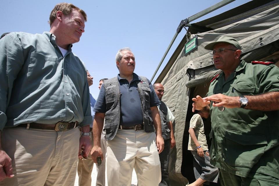 Canadian Foreign Affairs Minister John Baird, left,  listens to a Moroccan military medical officer  during his tour at Zaatari  camp for Syrian refugees with his  Jordanian counterpart Nasser Judeh, center, in Mafraq, Jordan, Saturday, Aug. 11, 2012.  (AP photo/Mohammad Hannon)