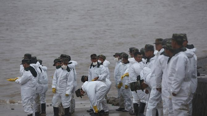 Paramilitary soliders stand on the banks near the site of a sunken ship in the Jianli section of Yangtze River