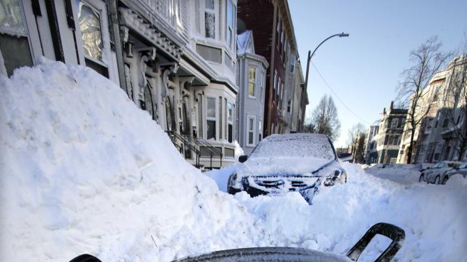 A trash can marks the cleared out parking spot of a resident on M street in the South Boston neighborhood of Boston early Sunday, Feb. 10, 2013 in Boston. (AP Photo/Gene J. Puskar)