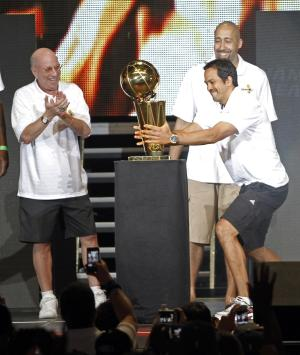 Miami Heat coach Erik Spoelstra, right, grabs the NBA championship trophy as assistant coaches Ron Rothstein, left, and David Frizdale watch, in Miami on Monday, June 25, 2012. Hundred of thousands of people filled the streets of Miami for the Heat championship parade, and then 15,000 more got into the arena afterward for a long, loud reception for the NBA's new kings. (AP Photo/Alan Diaz)