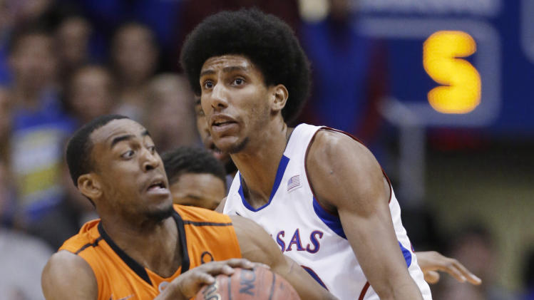 Oklahoma State guard Markel Brown (22) is fouled by Kansas forward Kevin Young (40) during the first half of an NCAA college basketball game in Lawrence, Kan., Saturday, Feb. 2, 2013. (AP Photo/Orlin Wagner)