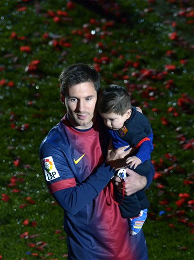 FC Barcelona's Lionel Messi, from Argentina, holds his baby after his team won the Spanish League after their La Liga soccer match against Valladolid at Camp Nou stadium in Barcelona, Sunday, May 19, 