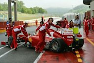 Ferrari F1 team members help Spanish driver Fernando Alonso into the pits of the Mugello track, during the fist day of the F1 official test session. Fernando Alonso&#39;s Ferrari overcame heavy rain which eventually triggered a premature end to the session to top the times at Tuesday&#39;s testing at Mugello