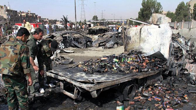 Syrian soldiers check a burned truck in front of a damaged military intelligence building where two bombs exploded, at Qazaz neighborhood in Damascus, Syria, on Thursday May 10, 2012. Two strong explosions ripped through the Syrian capital Thursday, killing or wounding dozens of people and leaving scenes of carnage in the streets in an assault against a center of government power. (AP Photo/Bassem Tellawi)