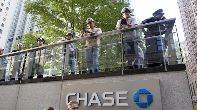 Police, pedestrians, and construction workers watch an Occupy Wall Street march from the JP Morgan Chase building grounds in the financial district, Monday, Sept. 17, 2012, in New York. A handful of Occupy Wall Street protestors were arrested during a march toward the New York Stock Exchange on the anniversary of the grass-roots movement. (AP Photo/John Minchillo)