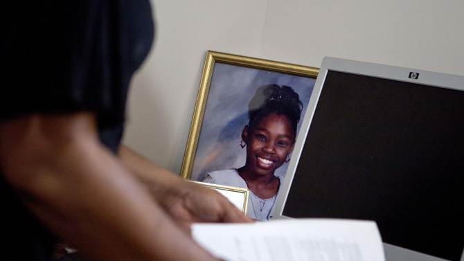 Patricia Jackson sifts  through bank documents as a picture of her daughter Nakawe sits on the desk in their home Saturday, June 16, 2012, in Marietta, Ga. On a suburban cul-de-sac northwest of Atlanta, the Jacksons are struggling to keep a house worth $100,000 less than they owe. Their voices and those of many others tell the story of a country that, for all the economic turmoil of the past few years, continues to believe things will get better. But until it does, families are trying to hang on to what they've got left. The Great Recession claimed nearly 40 percent of Americans' wealth, the Federal Reserve reported last week. The new figures, showing Americans' net worth has plunged back to what it was in 1992, left economists shuddering. (AP Photo/David Goldman)