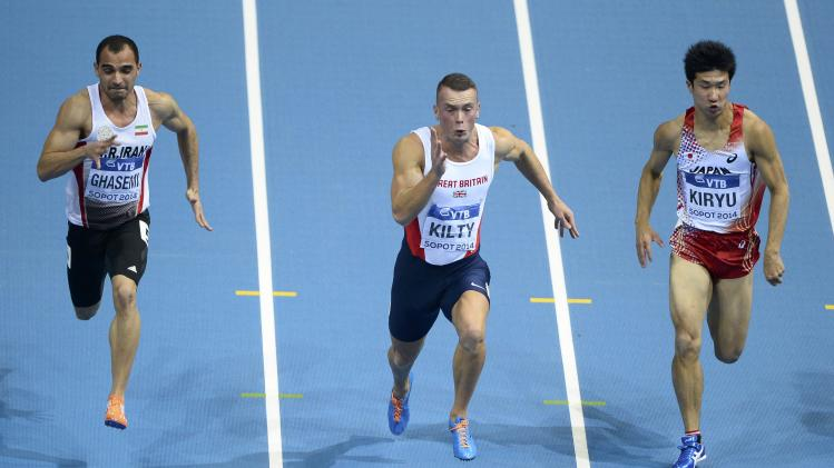 Ghasemi of Iran, Kilty of Britain and Kiryu of Japan compete during the men's 60 metres semi-final at the world indoor athletics championships at the ERGO Arena in Sopot