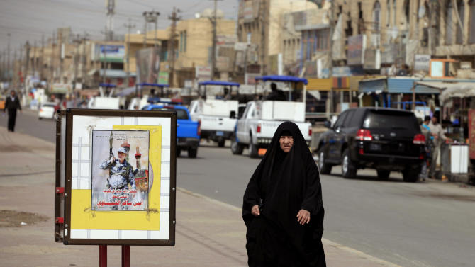 """In this Sunday, Feb. 24, 2013 photo, a woman walks past a poster showing a slain policeman in the Jihad neighborhood of west Baghdad, Iraq. Fliers claiming to be from a new Iranian-linked Shiite militant group began turning up last week in front of Iraqi Sunni households bearing a chilling message: Get out now or face """"great agony"""" soon.   (AP Photo/ Karim Kadim)"""