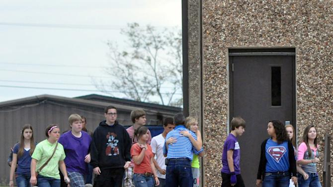 A Stillwater Junior High student hugs a member of the staff as her class is escorted to a waiting bus following the death of a student Wednesday, Sept. 26, 2012 in Stillwater, Okla. A 13-year-old student shot and killed himself in a hallway at an Oklahoma junior high school before classes began Wednesday, police said, terrifying teenagers who feared a gunman was on the loose. (AP Photo/The News Press,Chase Rheam)