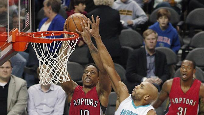 Toronto Raptors' DeMar DeRozan (10) looks to score as Charlotte Hornets' Gerald Henderson (9) goes for the block during the first half of an NBA basketball game in Charlotte, N.C., Friday, March 6, 2015. (AP Photo/Bob Leverone)