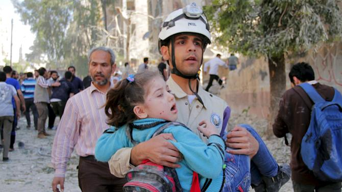 A civil defence member holds a rescued schoolgirl after what activists said was a barrel bomb dropped by forces loyal to Syria's President Bashar al-Assad and hit a school and a residential building in Seif al-Dawla neighborhood of Aleppo