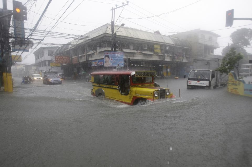 A passenger jeepney braves a flooded intersection brought by Typhoon Muifa in Manila, Philippines on Tuesday Aug. 2, 2011. Muifa continues to blow away from the northern Philippines after killing at least 4 people even though it did not make landfall. (AP Photo/Aaron Favila)