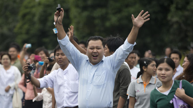 A man waves as people line the street to see U.S. President Barack Obama traveling in his motorcade to meet with Myanmar's President Thein Sein at Yangon Parliament Building in Yangon, Myanmar, Monday, Nov. 19, 2012. This is the first visit to Myanmar by a sitting U.S. president. (AP Photo/Carolyn Kaster)