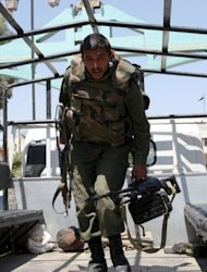 A Syrian soldier carries his weapons as he climbs off a truck escorting a UN peace observers convoy (unseen) on its way to the restive southern city of Daraa just before a roadside bomb attack targeted them