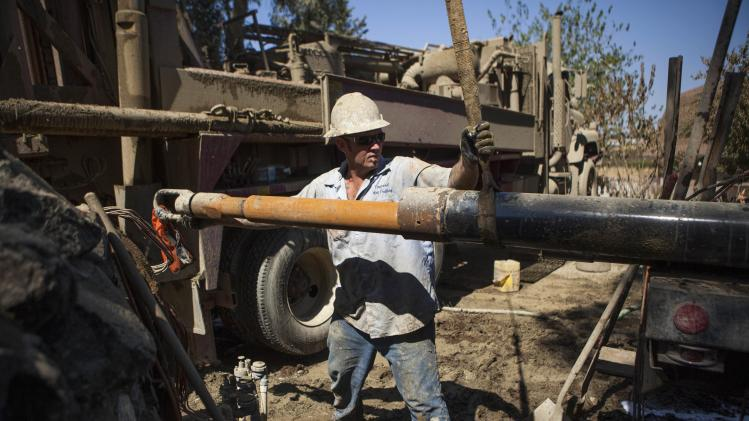 Drill helper Jimmy Payne rigs another 20-foot section of pipe as they work to deepen the Brady family well in Woodland, California
