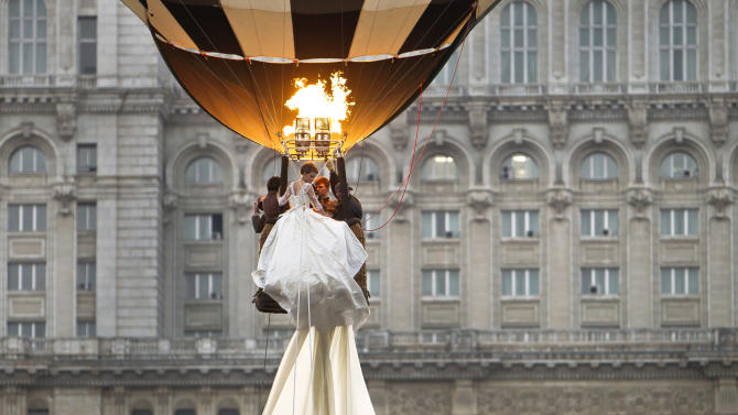 A model rides in a hot air balloon to show the world's longest wedding dress train during a Guinness World Record attempt in Bucharest, Romania, Tuesday, March 20, 1012. Romania has set the world record for the world's longest bridal train. The nearly 3-kilometer (1.86-mile) long ivory train, which took 100 days to stitch, was showcased dramatically on Tuesday on the boulevard leading up to the giant palace built by late dictator Nicolae Ceausescu, seen in background. The previous record was 2.488 Km. (AP Photo/Vadim Ghirda)