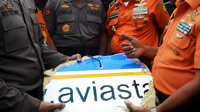 A part of the Aviastar airplane body is handed over from the policemen to the members of the rescue team at Ulu Salu village in Luwu