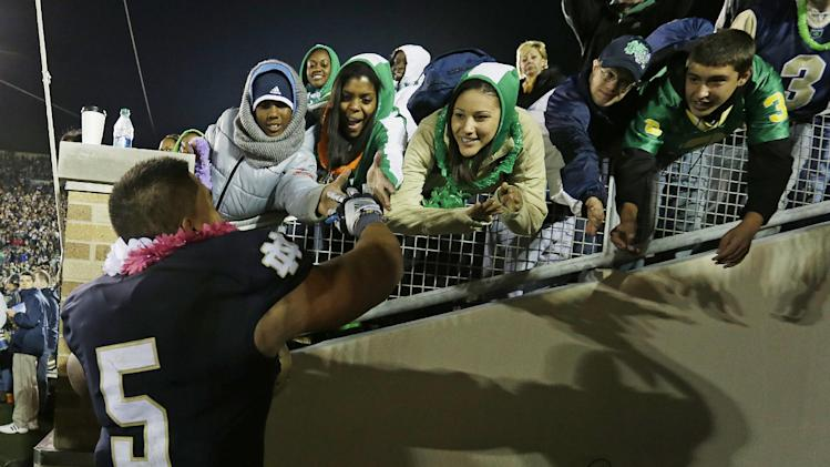 In this Sept. 22, 2012 photo,  Notre Dame's Manti Te'o (5) celebrates with fans after Notre Dame defeated Michigan, 13-6, in an NCAA college football game in South Bend, Ind. Notre Dame defensive coordinator Bob Diaco believes Te'o is the finest football player in college. (AP Photo/Darron Cummings)