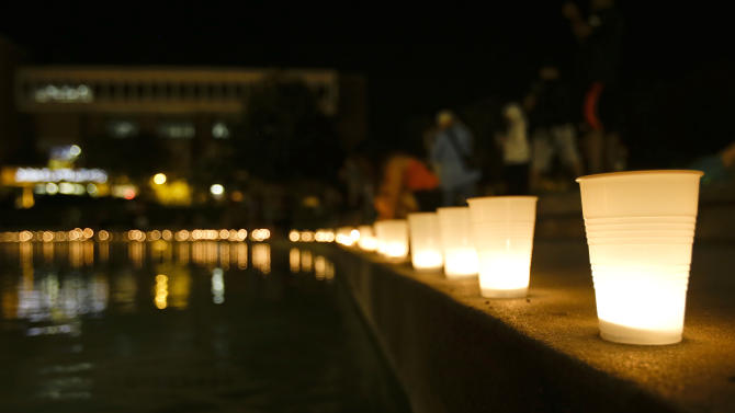 Candles line a wall around a reflection pond at the University of Central Florida to honor Steven Sotloff