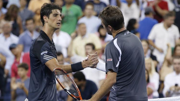 Stan Wawrinka of Switzerland shakes hands with Thomaz Bellucci of Brazil after winning a 4th set tie-break to end their match at the 2014 U.S. Open tennis tournament in New York