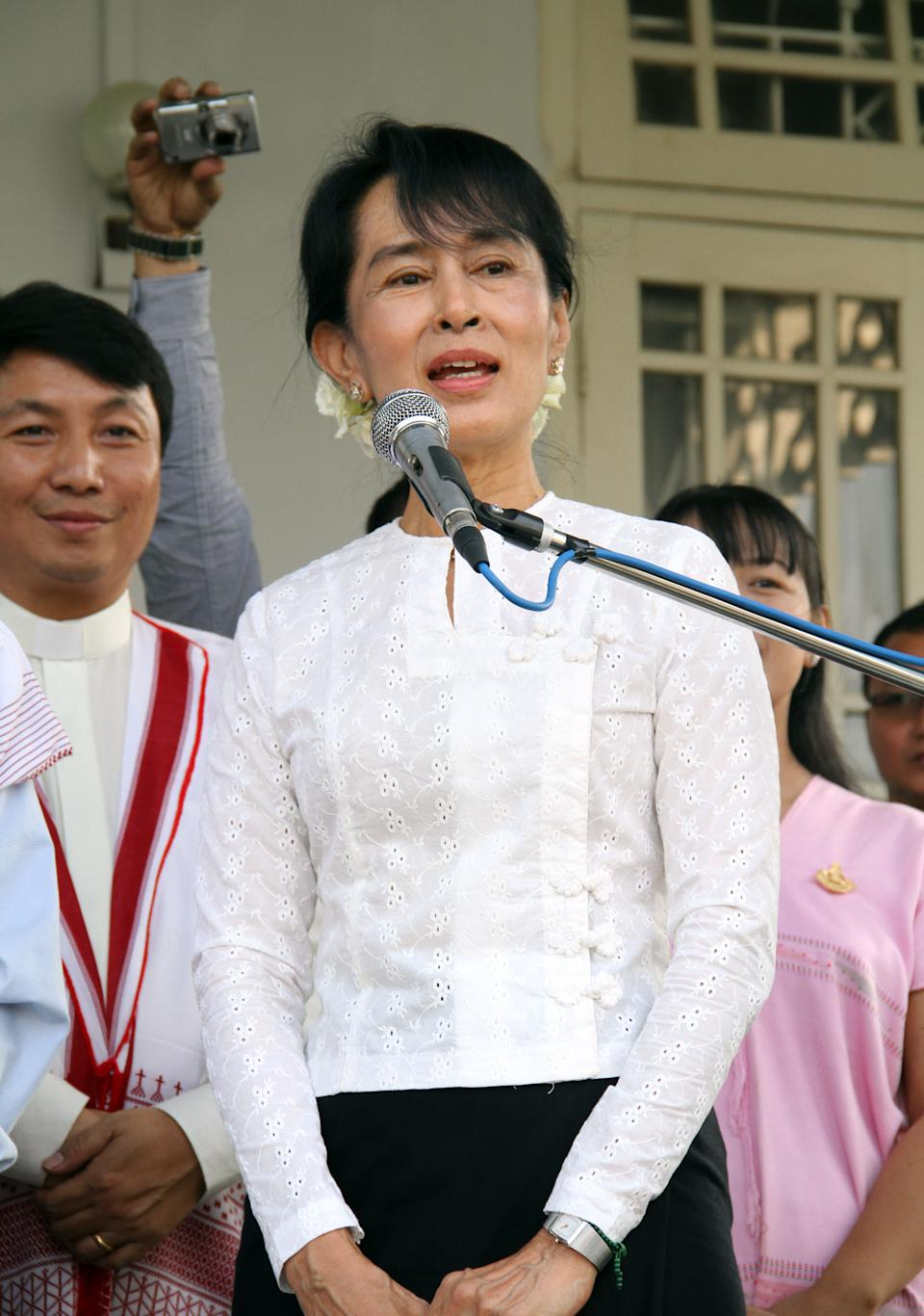 Myanmar's pro-democracy leader Aung San Suu Kyi talks to media after meeting with Saw Htay Maung, chairman of the KNU/KNLA, at her house on Friday, Feb. 10, 2012. (AP Photo/Khin Maung Win)