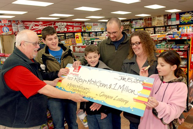 <p>               The Gunn family of Wolf Creek, Ore., accepts a symbolic check for $1 million before taxes from Oregon Lottery official Ray Martin on Tuesday, Jan. 15, 2013, at the convenience store where they bought it in Merlin, Ore. Riley Gunn lost his job as a project manager for a telecommunications company in May 2012 and moved his family to a one-room cabin outside Wolf Creek, Ore. While he and his wife were driving home, they pulled off the freeway for corn dogs and pizza pockets and bought an $8 ticket, and won $1 million dollars. Riley and Misti Gunn are at center, with their sons Elijah, 13, left, and Isac, 11, and daughter, Destenie, 9, right. (AP Photo/Jeff Barnard)