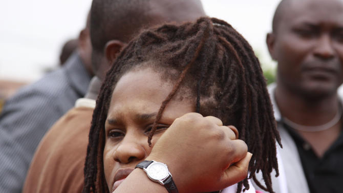 A woman who lost a family member in a plane crash waits to identify bodies at the Lagos state university teaching hospital in Lagos, Nigeria, Tuesday, June 5, 2012. A commercial airliner crashed into a densely populated neighborhood in Nigeria's largest city on Sunday, killing all 153 people on board and others on the ground in the worst air disaster in nearly two decades for the troubled nation. (AP Photo/Sunday Alamba)
