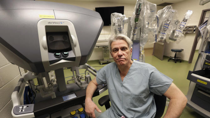 In this March 22, 2013 photo, Dr. Pier Giulianotti, chief of minimally invasive and robotic surgery at the University of Illinois Hospital & Health Sciences System in Chicago, sits at the control panel of the da Vinci robot system. Surgeons say the advantages of the system include allowing them to operate sitting down, using small robotic hands with no tremor. But critics say a big increase in robot operations nationwide is due to heavy marketing and hype, and the U.S. Food and Drug Administration is looking into problems and deaths that may be linked with robotic surgery. (AP Photo/M. Spencer Green)