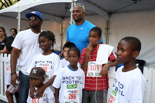 Former NFL wide receiver Amani Toomer, center back row, is seen during the National Football League Back to Football Run on Friday, Aug. 30, 2012 at Central Park in New York. (John Minchillo/AP Images