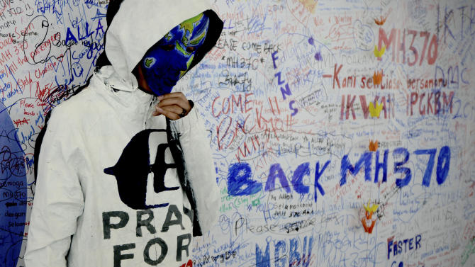 """An unidentified woman with her face painted, depicting the flight of the missing Malaysia Airline, MH370, poses in front of the """"wall of hope"""" at Kuala Lumpur International Airport in Sepang, Malaysia, Monday, March 17, 2014. Authorities now believe someone on board the Boeing 777 shut down part of the aircraft's messaging system about the same time the plane with 239 people on board disappeared from civilian radar. But an Inmarsat satellite was able to automatically connect with a portion of the messaging system that remained in operation, similar to a phone call that just rings because no one is on the other end to pick it up and provide information. No location information was exchanged, but the satellite continued to identify the plane once an hour for four to five hours after it disappeared from radar screens. (AP Photo/Joshua Paul)"""