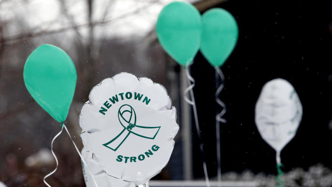 FILE - In this Dec. 14, 2013 file photo, Balloons fly outside a doctor's office on the first anniversary of the Sandy Hook massacre, in Newtown, Conn., Saturday, Dec. 14, 2013. Newtown officials are applying for a federal grant and charities are pooling their resources in an attempt to ensure that free mental health care remains available to those who need it following the December 2012 massacre at the Sandy Hook Elementary School. The moves come as some charities begin to run out of money. Officials say they have no real idea of how much they will ultimately need for mental health care in Newtown, and for how many years. (AP Photo/Robert F. Bukaty)
