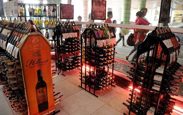 "Pedestrians walk past a store selling alcoholic beverages at a mall in Manila on January 1, 2013. A ""sin tax"" on cigarettes and alcohol dampened the New Year party spirit when it was introduced in the Philippines on January 1, as part of a government bid to boost finances"