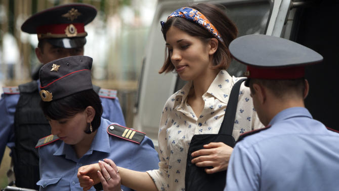 """Nadezhda Tolokonnikova, centre, a member of feminist punk group Pussy Riot is escorted to a court room in Moscow, Russia, Tuesday, Aug. 7, 2012. Russia's President Vladimir Putin on Thursday criticized the feminist punk rockers facing trial for performing a """"punk prayer"""" against him at Moscow's main cathedral, but said that a punishment for them shouldn't be too severe. (AP Photo/Alexander Zemlianichenko)"""