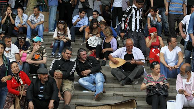 Protesters sit on the steps of Gezi Park of Taksim Square in Istanbul, Saturday, June 15, 2013. Protesters will press on with their sit-in at an Istanbul park, an activist said Saturday, defying government appeals and a warning from Prime Minister Recep Tayyip Erdogan for the two-week standoff that has fanned nationwide demonstrations to end. (AP Photo/Thanassis Stavrakis)