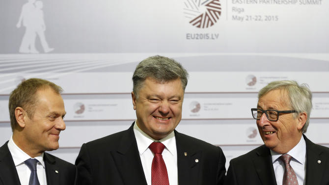 European Commission President Jean-Claude Juncker, right, and European Council President Donald Tusk, left, greet Ukrainian President Petro Poroshenko during arrivals at the Eastern Partnership summit in Riga, on Friday, May 22, 2015. EU leaders gather for a second day of meetings with six post-communist nations to discuss various issues, including enlargement, the economy and Ukraine. (AP Photo/Mindaugas Kulbis)