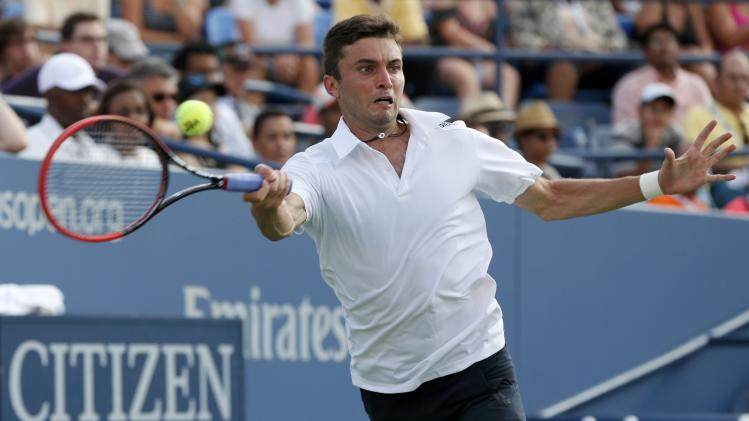Simon of France returns to Cilic of Croatia during their fourth round match at the 2014 U.S. Open tennis tournament in New York