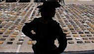 "A Colombian policewoman stands by packages of cocaine, part of a seizure worth $3 million from the ""Los Urabenos"" gang, in Rioacha, Guajira deparment, Colombia, in September 2012. One of Colombia's most notorious drug kingpins, Henry de Jesus Lopez Londono, has been arrested in a suburb of Buenos Aires, police in Argentina said Wednesday"