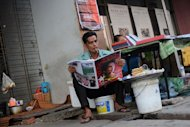 A man reads a newspaper in Yangon, March 10, 2013. Myanmar's public has become accustomed to an increasingly boisterous media since the country's quasi-civilian government relaxed its grip on the press after coming to power in 2011