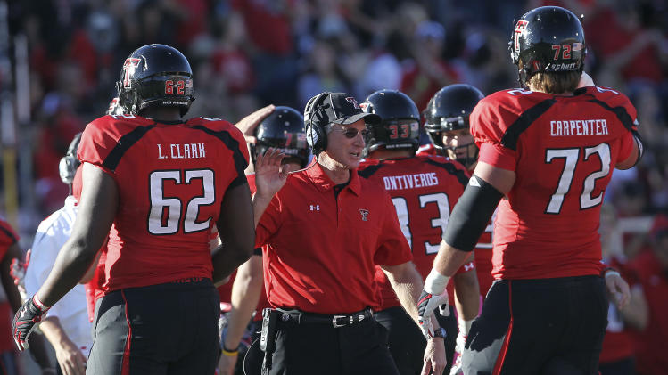 Texas Tech head coach Tommy Tuberville greets Le'Raven Clark (62) and Beau Carpenter (72) during their NCAA college football game against West Virginia in Lubbock, Texas, Saturday, Oct. 13, 2012. (AP Photo/Lubbock Avalanche-Journal, Stephen Spillman) LOCAL TV OUT