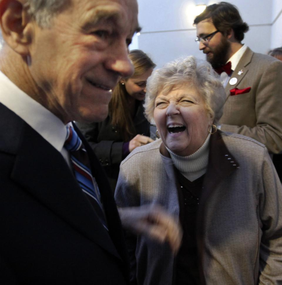 Carol Paul, left, wife of Republican presidential candidate Rep. Ron Paul, R-Texas, laughs at her husband's remark before he addresses a crowd at the North Dakota caucus Tuesday, March 6, 2012, in Fargo, N.D. (AP Photo/Charles Rex Arbogast)