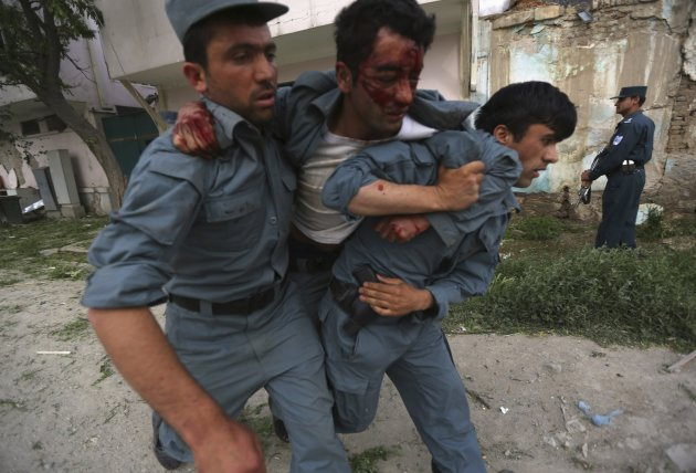 A wounded Afghan policeman is being carried away from the site of an explosion in Kabul