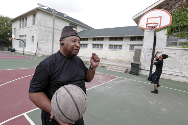 Bishop T.T. Turner of Mount Sinai Baptist Church, left, and 26-year-old Cleo Miller plays basketball in Cornell Square Park Friday, Sept. 20, 2013, in Chicago. The park was the scene of a late-night a